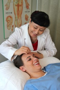 Dr. Diana Tong Li with Julia, placing acupuncture needle in 'the third eye'